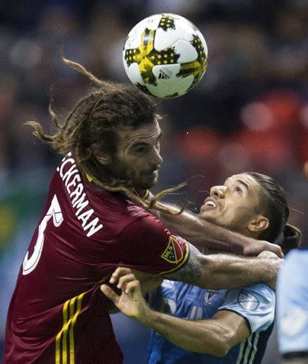 Real Salt Lake's Kyle Beckerman, left, and Vancouver Whitecaps' Nicolas Mezquida vie for the ball during the second half of an MLS soccer match Saturday, Sept. 9, 2017, in Vancouver, British Columbia. (Darryl Dyck/The Canadian Press via AP)