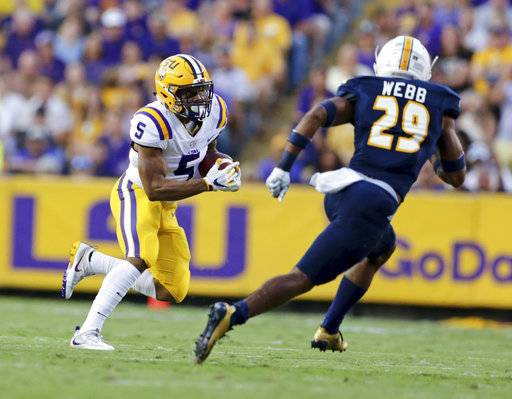 LSU running back Derrius Guice (5) is pursued by Chattanooga defensive back Lucas Webb (29) during the first half of an NCAA college football game in Baton Rouge, La., Saturday, Sept. 9, 2017. (AP Photo/Rusty Costanza)