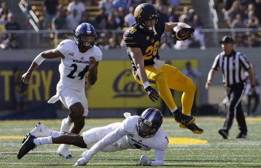 California running back Patrick Laird (28) jumps over Weber State safety Trey Hoskins during the second half of an NCAA college football game in Berkeley, Calif., Saturday, Sept. 9, 2017. (AP Photo/Jeff Chiu)