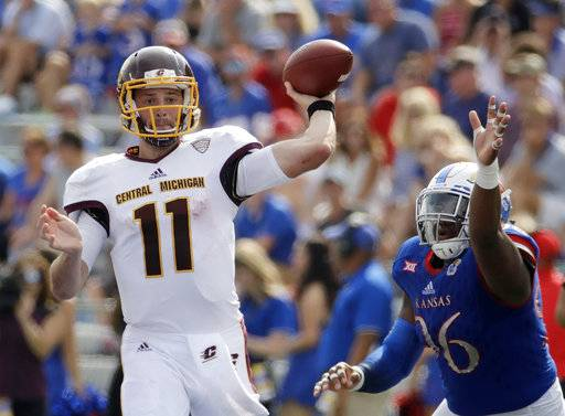 Central Michigan quarterback Shane Morris (11) throws under pressure from Kansas defensive tackle Daniel Wise (96) during the first half of an NCAA college football game, Saturday, Sept. 9, 2017, in Lawrence, Kan. (AP Photo/Charlie Riedel)