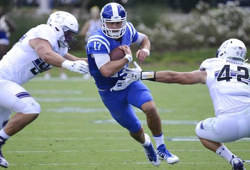 Duke quarterback Daniel Jones runs between Northwestern's Paddy Fisher (42) and Tommy Camifax during an NCAA college football game, Saturday, Sept. 9, 2017, in Durham, N.C. (Bernard Thomas/The Herald-Sun via AP)