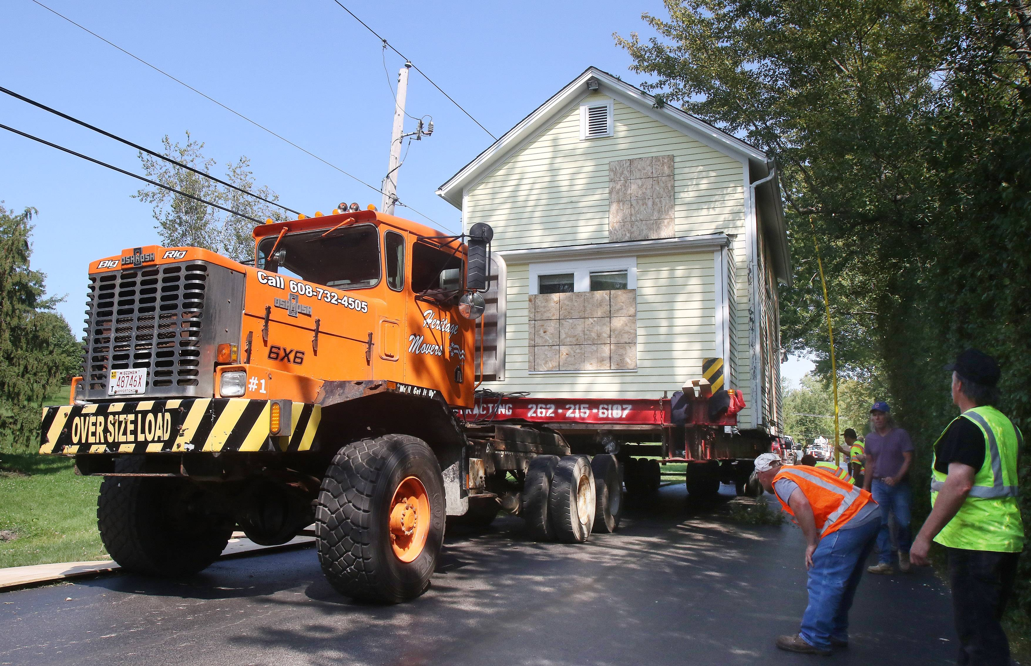 A 19th century house is moved Sunday through Barrington on its way to a new site in Barrington Hills.