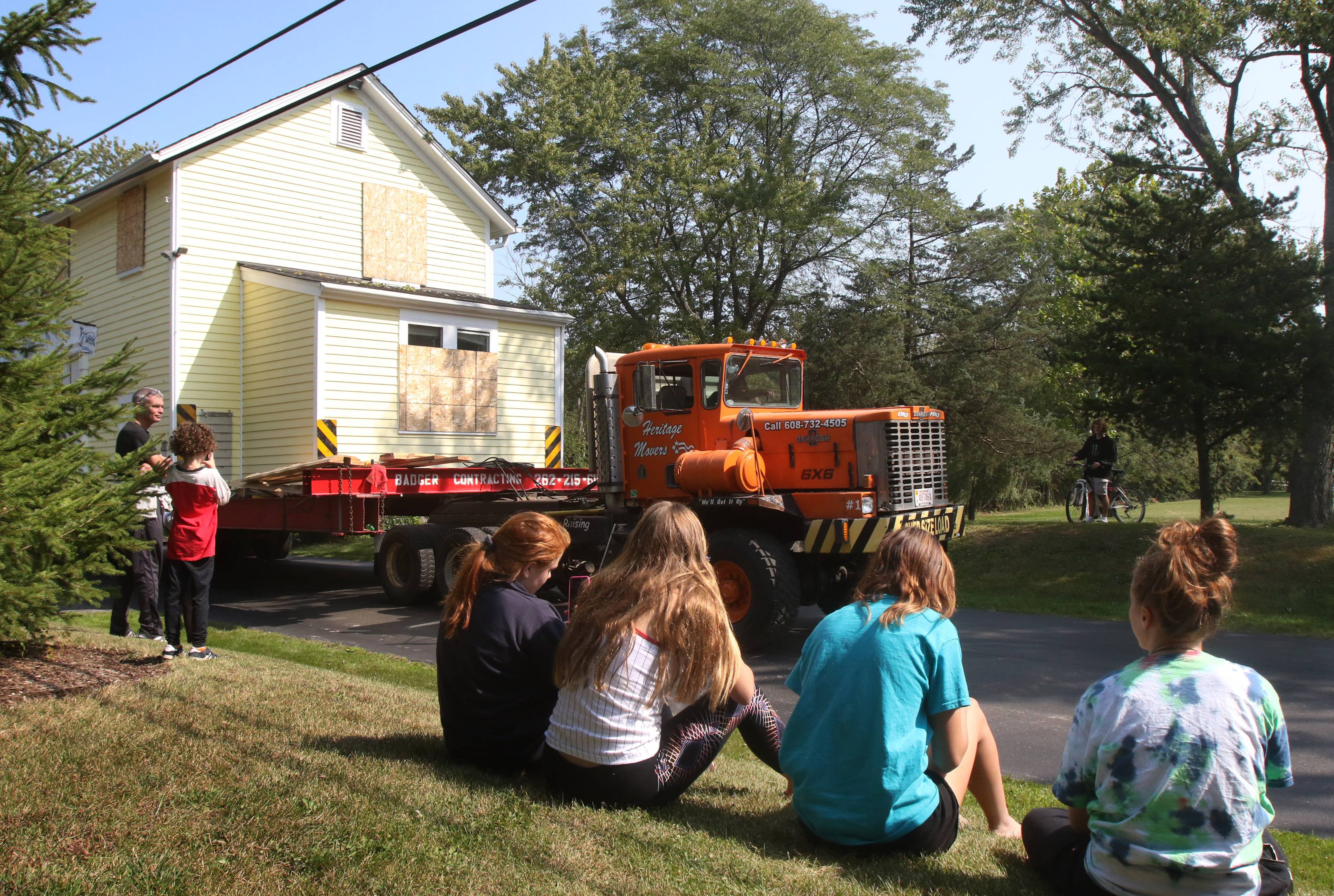 Spectators watch as a 19th century house is moved Sunday from Barrington to a new site in Barrington Hills.