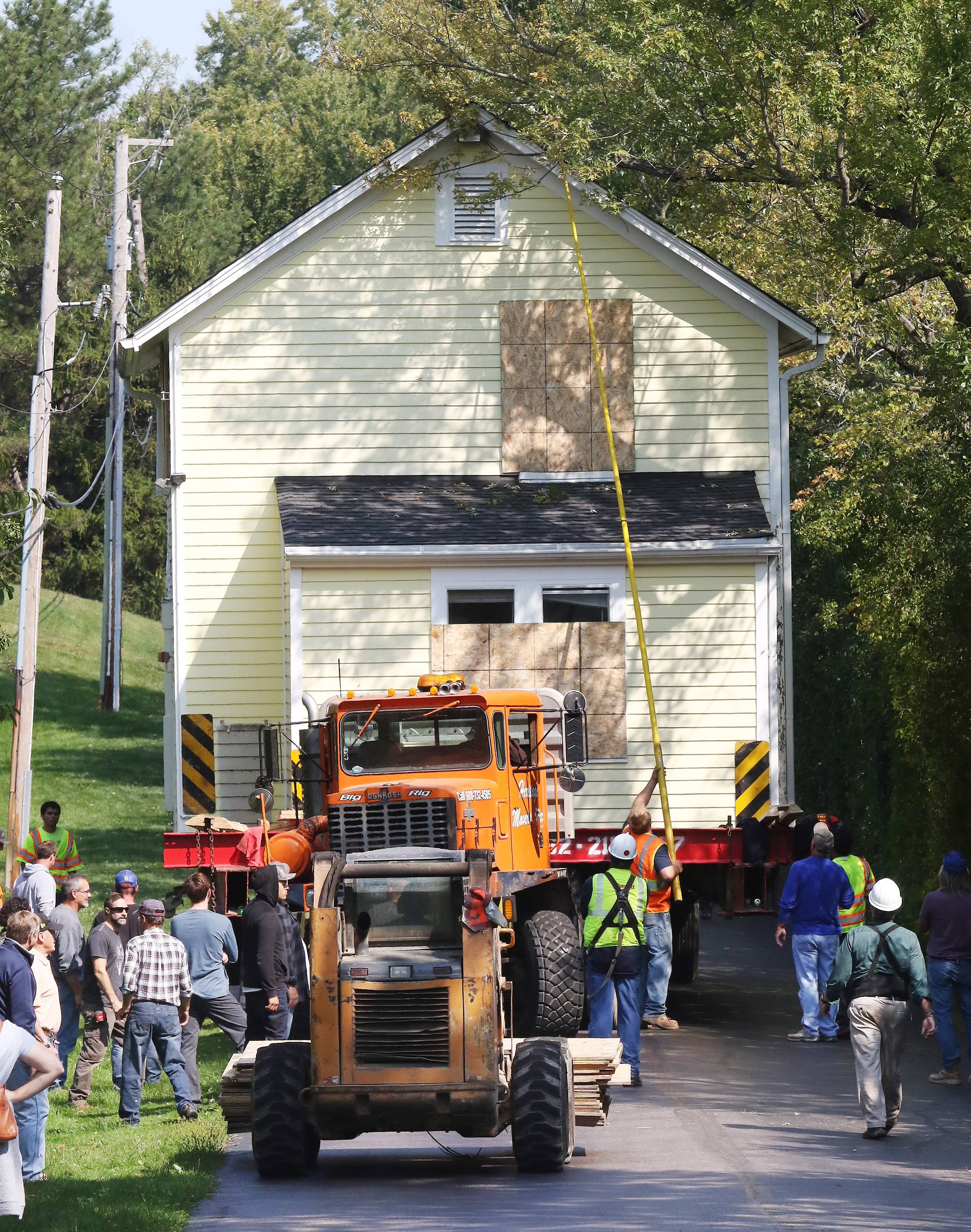 Rerouting utility lines and dodging tree limbs required a house move to proceed at a snail's pace Sunday. The 19th century house paraded through Barrington en route to a new site in Barrington Hills.
