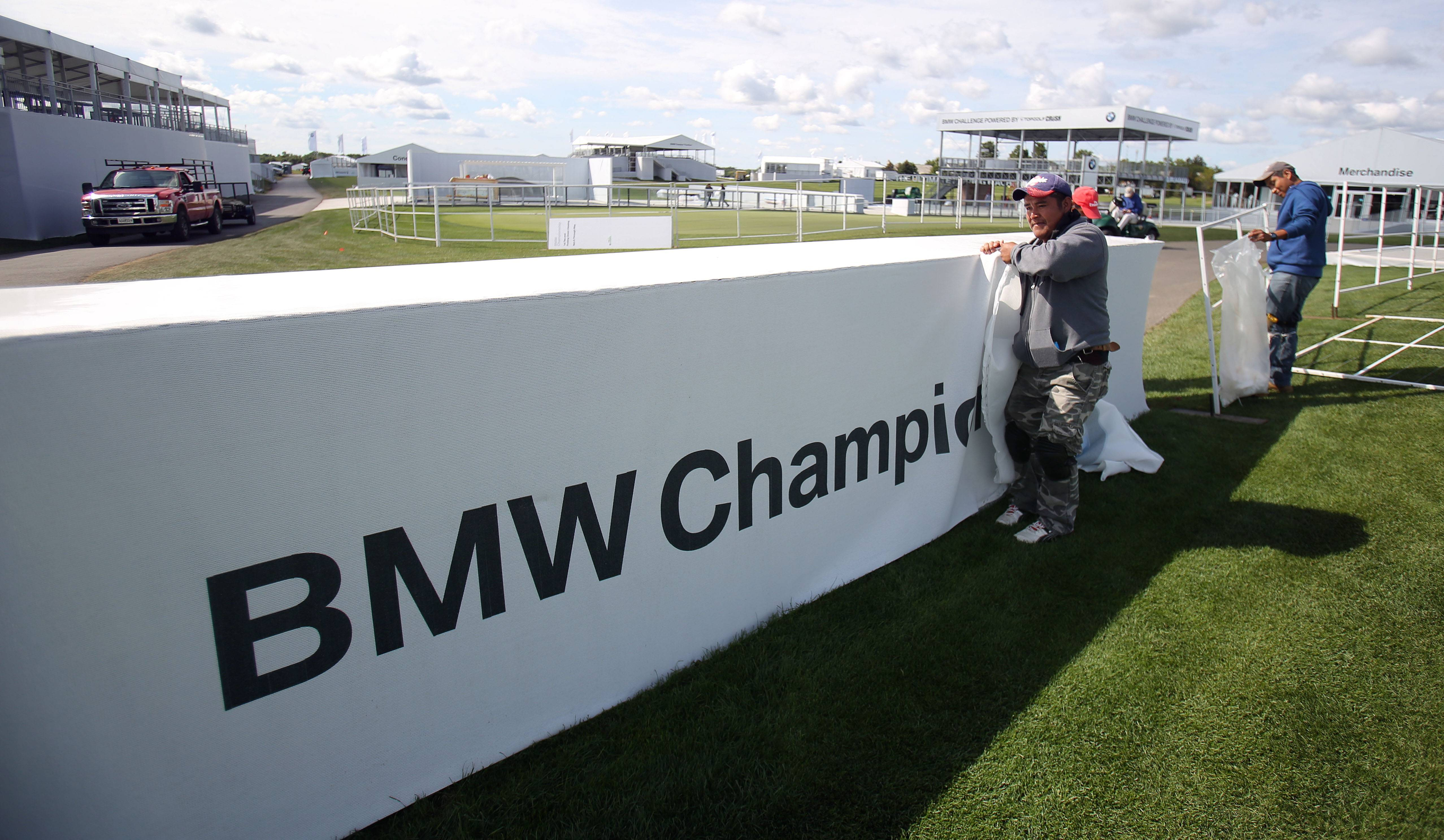 Gustino Rodriguez puts up a sign last week in preparation for this week's BMW Championship golf tournament at Conway Farms in Lake Forest.