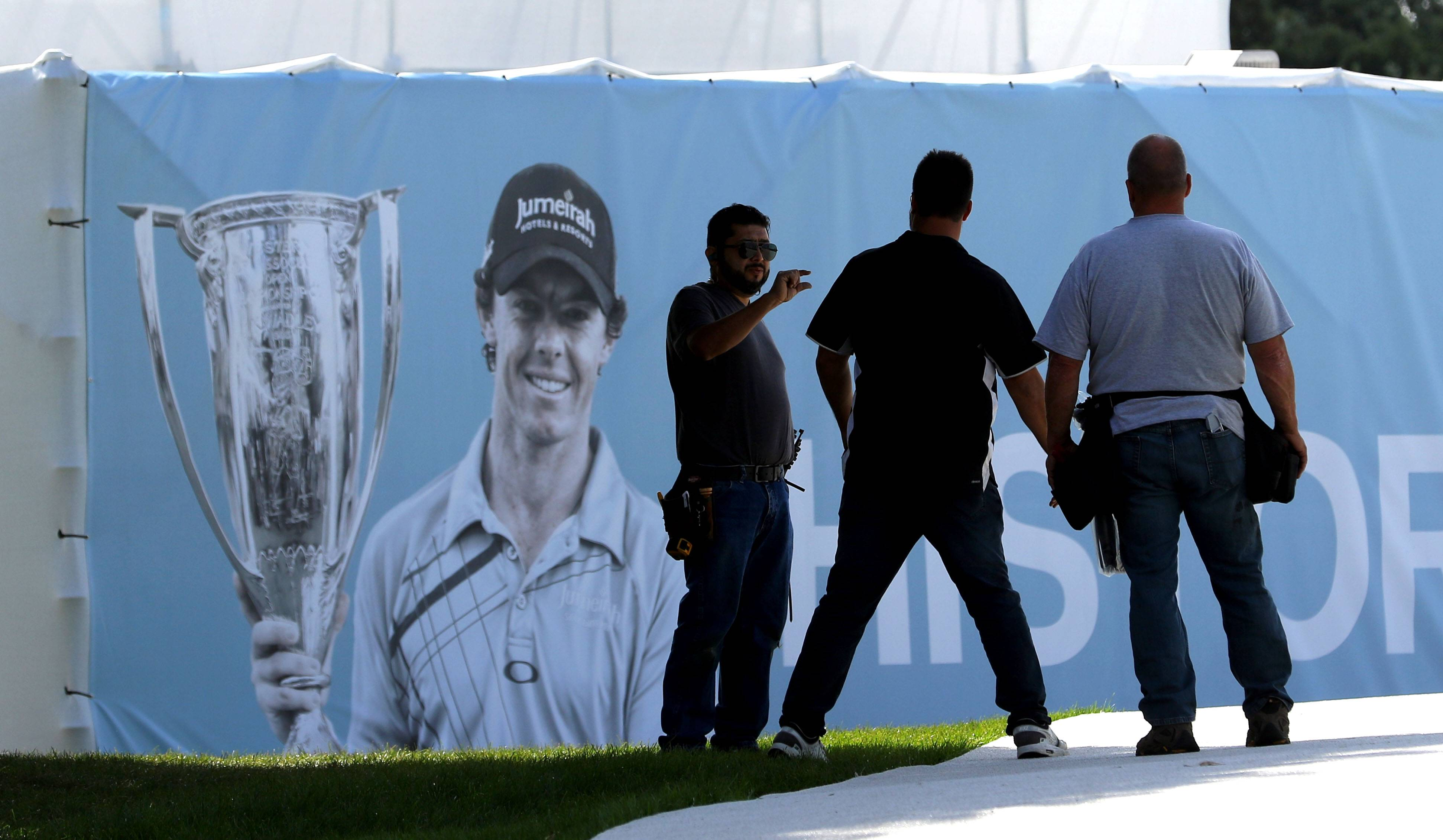 Workers hang banners at Conway Farms in Lake Forest, which will host the BMW Championship golf tournament this week.