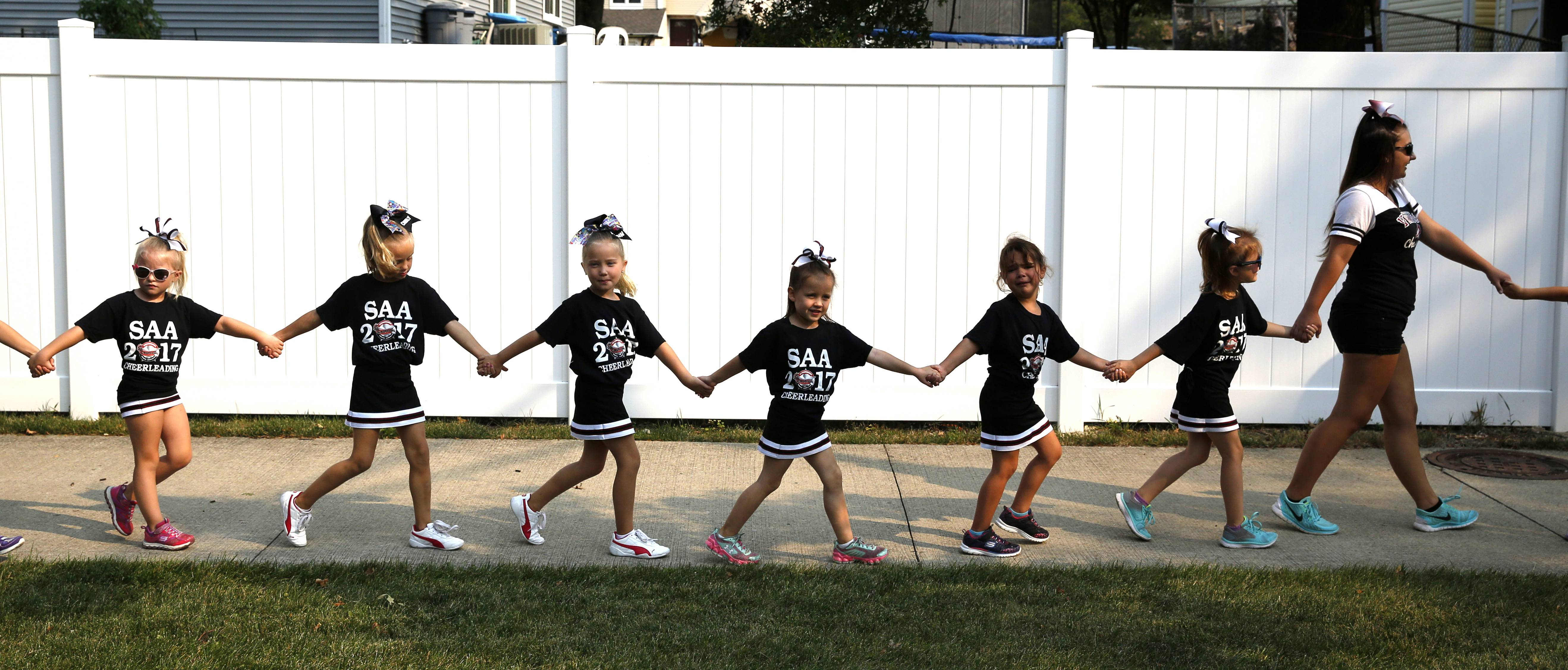 Members of the 2017 Schaumburg Athletic Association 5-6-year-old cheerleaders make their way to the Schaumburg Septemberfest parade route.