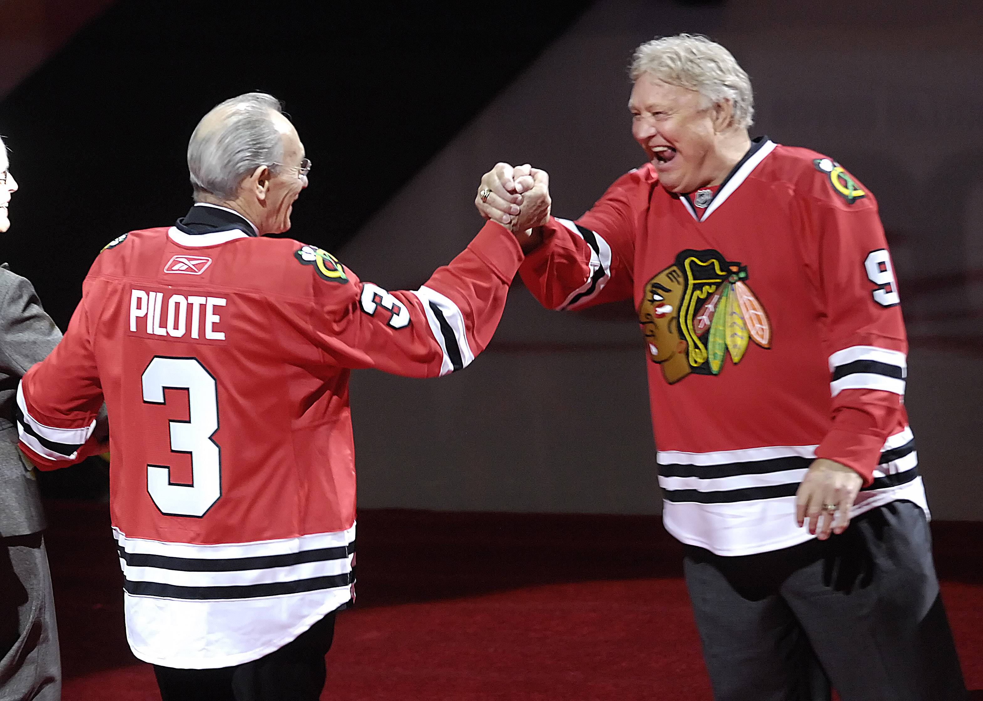 Chicago Blackhawks legend Bobby Hull greets Pierre Pilote during a number retirement ceremony for Pilote and the late Keith Magnuson before the game with the Boston Bruins Wednesday at the United Center.