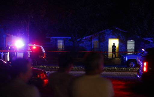 Onlookers watch police work the scene of a shooting at a home in Plano, north of Dallas, Texas, Sunday night, Sept. 10, 2017. Authorities in North Texas say several people are dead, including the suspect, after a shooting at the Plano home. (Vernon Bryant/The Dallas Morning News via AP)