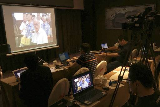 Reporters watch a screen showing a video footage of detained Taiwanese activist Lee Ming-Che testifying at his trial at the Yueyang Intermediate People's Court in Yueyang, south China's Hunan province, Monday, Sept. 11, 2017. The trial of the Taiwanese activist accused of subversion of state power began Monday in central China, the first prosecution of a nonprofit worker on criminal charges since Beijing passed a law tightening controls over foreign non-governmental organizations. (AP Photo/Emily Wang)