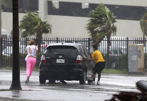 Stranded motorists try to get back in their car after a breakdown as Hurricane Irma bears down on the Florida Keys, Sunday, Sept. 10, 2017, in Hialeah, Fla. Wind gusts of 82 mph were reported in Miami. (AP Photo/Alan Diaz)
