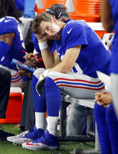 New York Giants quarterback Eli Manning sits on the sideline in the first half of an NFL football game against the Dallas Cowboys on Sunday, Sept. 10, 2017, in Arlington, Texas. (AP Photo/Michael Ainsworth)