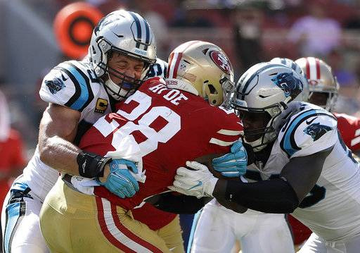 San Francisco 49ers running back Carlos Hyde (28) is tackled by Carolina Panthers middle linebacker Luke Kuechly, left, and outside linebacker Thomas Davis during the second half of an NFL football game in Santa Clara, Calif., Sunday, Sept. 10, 2017. (AP Photo/Marcio Jose Sanchez)