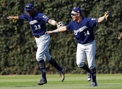 Milwaukee Brewers' Hernan Perez, right, and teammate Keon Broxton celebrate their win over the Chicago Cubs in a baseball game Sunday, Sept. 10, 2017, in Chicago. (AP Photo/Jim Young)