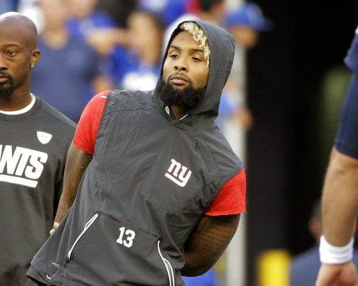 FILE - In this Aug. 31, 2017, file photo, New York Giants wide receiver Odell Beckham watches his teammates warm up before an NFL preseason football game against the New England Patriots, in Foxborough, Mass. Beckham Jr. has been listed as questionable for the Giants' season opener against the Cowboys in Dallas on Sunday night. Questionable in NFL terminology is a 50-50 chance to play.(AP Photo/Steven Senne, File)