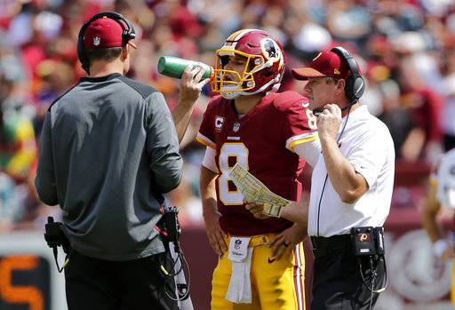 Washington Redskins head coach Jay Gruden, right, speaks with quarterback Kirk Cousins (8) during a break in play in the first half of an NFL football game against the Philadelphia Eagles, Sunday, Sept. 10, 2017, in Landover, Md. (AP Photo/Mark Tenally)