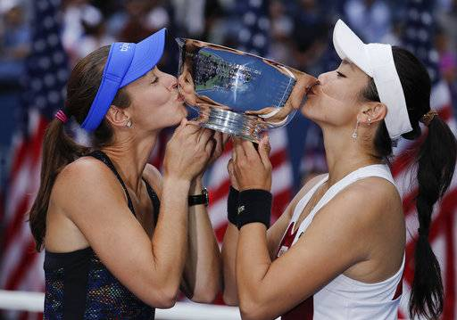 Martina Hingis, of Switzerland, left, and Chan Yung-Jan, of Taiwan, hold up the women's doubles championship trophy after beating Katerina Siniakova, of Czech Republic, and Lucie Hradecka, of the Czech Republic, in the women's doubles final of the U.S. Open tennis tournament, Sunday, Sept. 10, 2017, in New York. (AP Photo/Julie Jacobson)