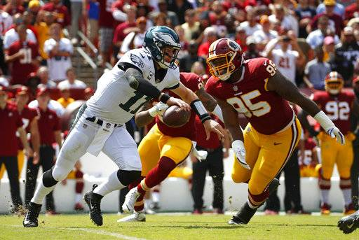 Philadelphia Eagles quarterback Carson Wentz, left, tries to outrun Washington Redskins defensive end Jonathan Allen (95) and outside linebacker Preston Smith as he looks for a receiver in the first half of an NFL football game, Sunday, Sept. 10, 2017, in Landover, Md. (AP Photo/Alex Brandon)