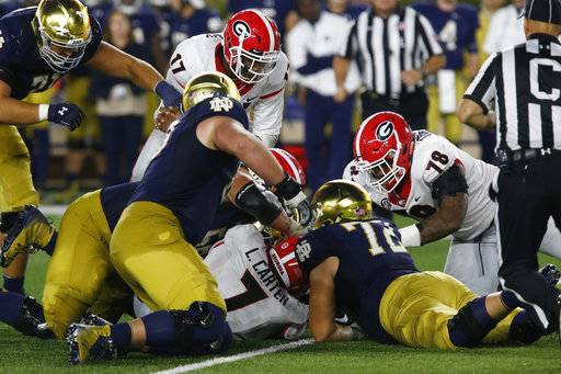 Georgia and Notre Dame players fight over a fumble caused by Georgia outside linebacker Davin Bellamy (17) during the second half of an NCAA college football game in South Bend, Ind., Saturday, Sept. 9, 2017. (Joshua L. Jones/Athens Banner-Herald via AP)