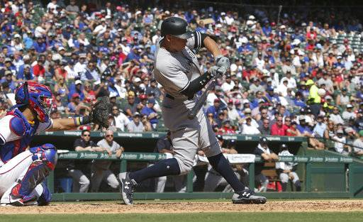 New York Yankees Aaron Judge, right, turns to hit a solo home run in front of Texas Rangers catcher Robinson Chirinos during the fourth inning of a baseball game in Arlington, Texas, Sunday, Sept. 10, 2017. (AP Photo/LM Otero)