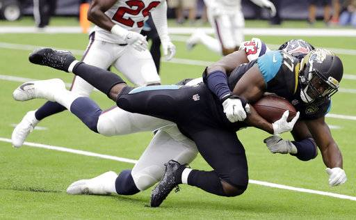 Jacksonville Jaguars running back Leonard Fournette (27) is hit by Houston Texans defensive end Joel Heath (93) during the first half of an NFL football game Sunday, Sept. 10, 2017, in Houston. (AP Photo/David J. Phillip)