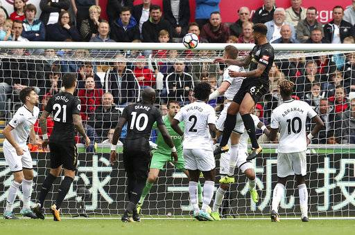 Newcastle United's Jamaal Lascelles, top right, scores against Swansea City during the English Premier League soccer match at the Liberty Stadium, Swansea, Wales, Sunday Sept. 10, 2017. (Nick Potts/PA via AP)