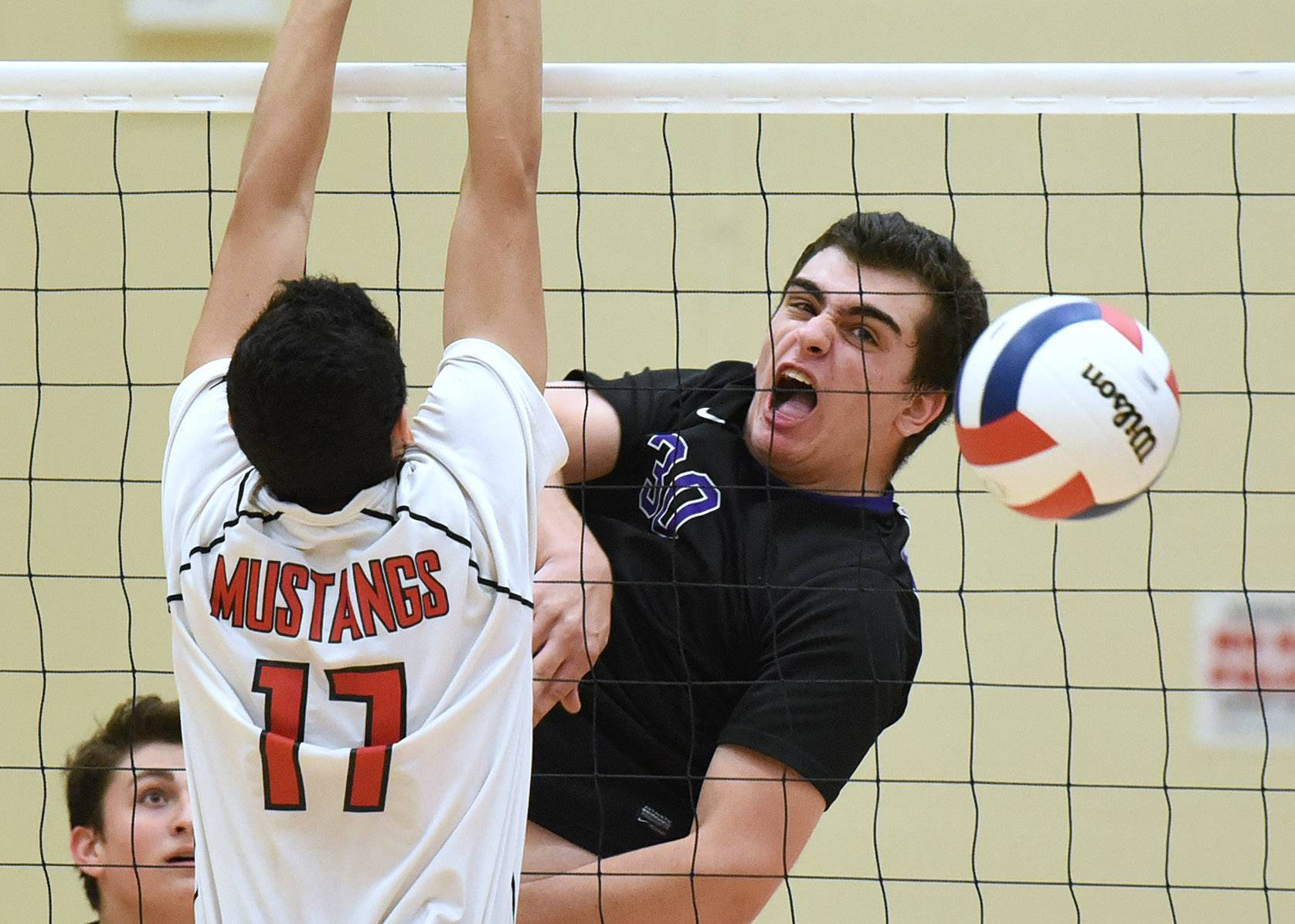 Rolling Meadows's Kyle Kornblum spikes the ball past Mundelein's Marc Rey during a regional volleyball match in Libertyville. Rolling Meadows won the match in two games.