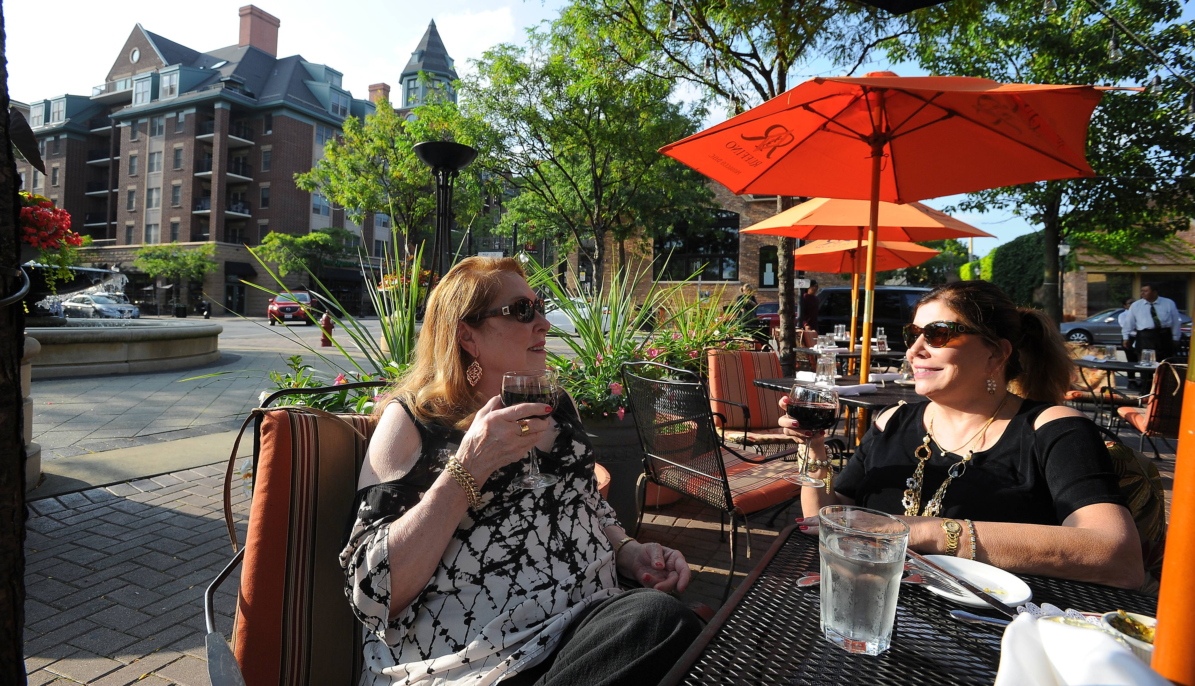 Karen Valdes of Hawthorn Woods, left, and her friend Michelle Downie of Oklahoma enjoy eating al fresco in downtown Arlington Heights.