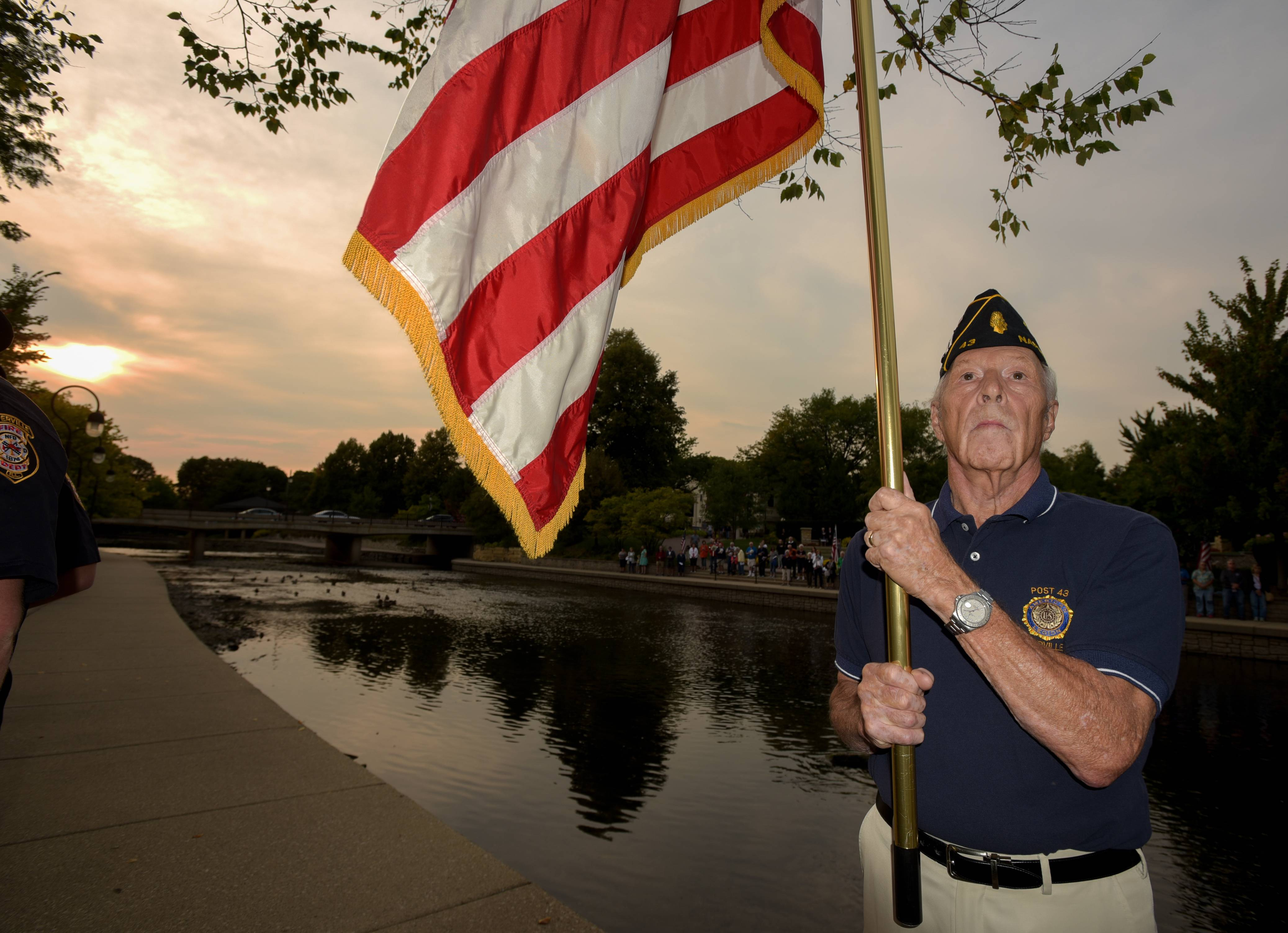 Jim Sarns of American Legion Post 43 posts colors Monday during Naperville's Sept. 11 remembrance ceremony at the Cmdr. Dan Shanower Memorial along the Riverwalk.