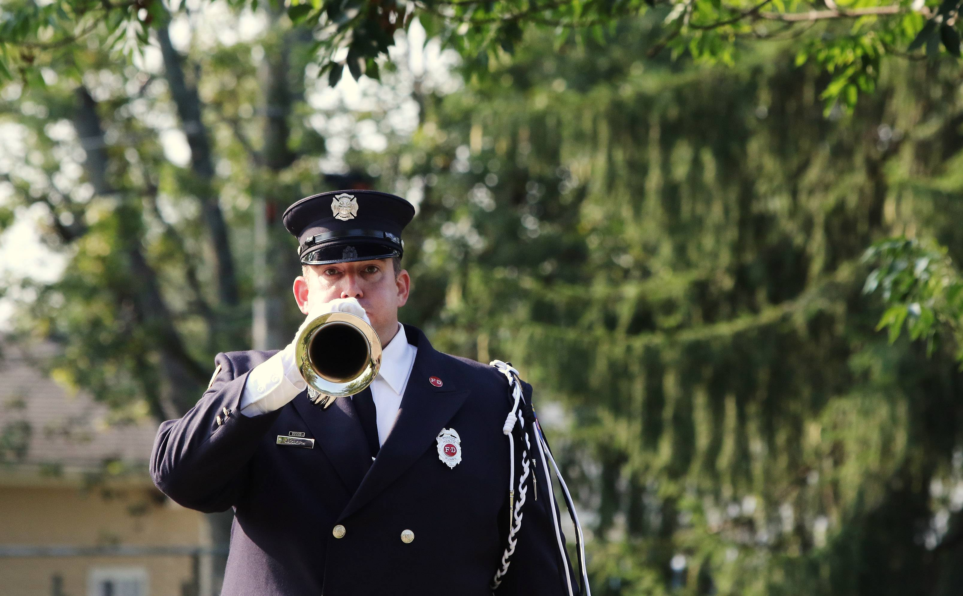 "Waukegan firefighter Michael Joseph plays ""Taps"" during the 9/11 Remembrance Ceremony at Fireman's Memorial Park in Waukegan on Monday. The Waukegan Fire Department hosted the event that recognized firefighters and police officers lost in the Sept. 11, 2001 terrorist attacks."