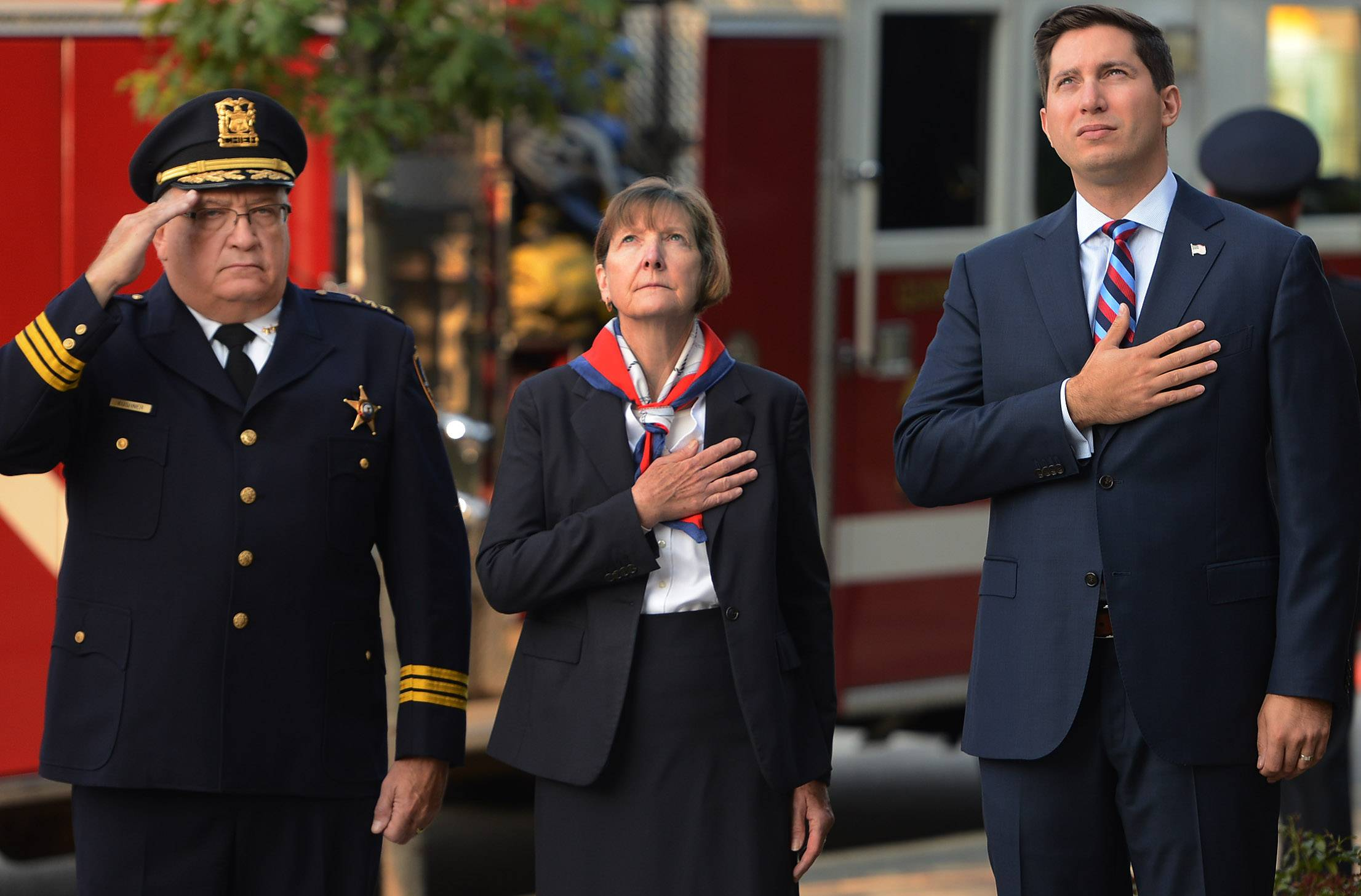 Des Plaines Police Chief William Kushner, left, Police and Fire Commissioner Deb Lester, and Mayor Matt Bogusz stand at attention during the playing of taps during the Sept. 11 remembrance ceremony in Des Plaines at city hall.