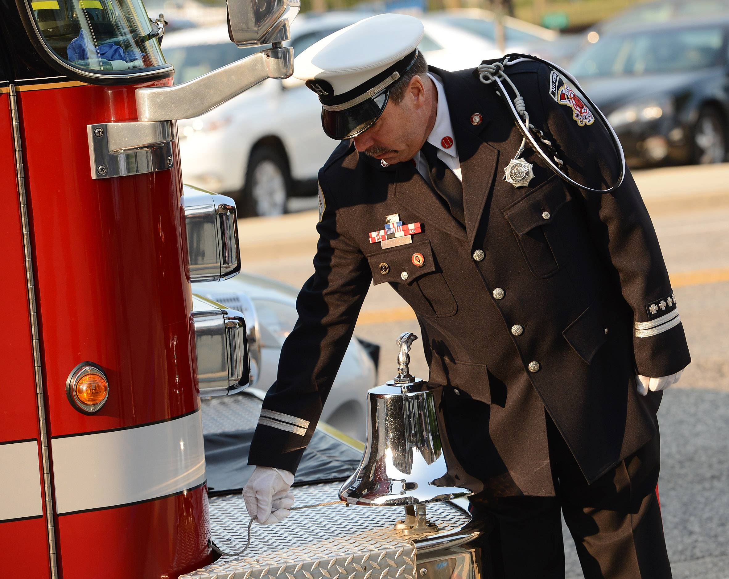 Des Plaines Fire Capt. Scott Peirson rings the ceremonial bell during the Sept. 11 remembrance ceremony at Des Plaines City Hall.