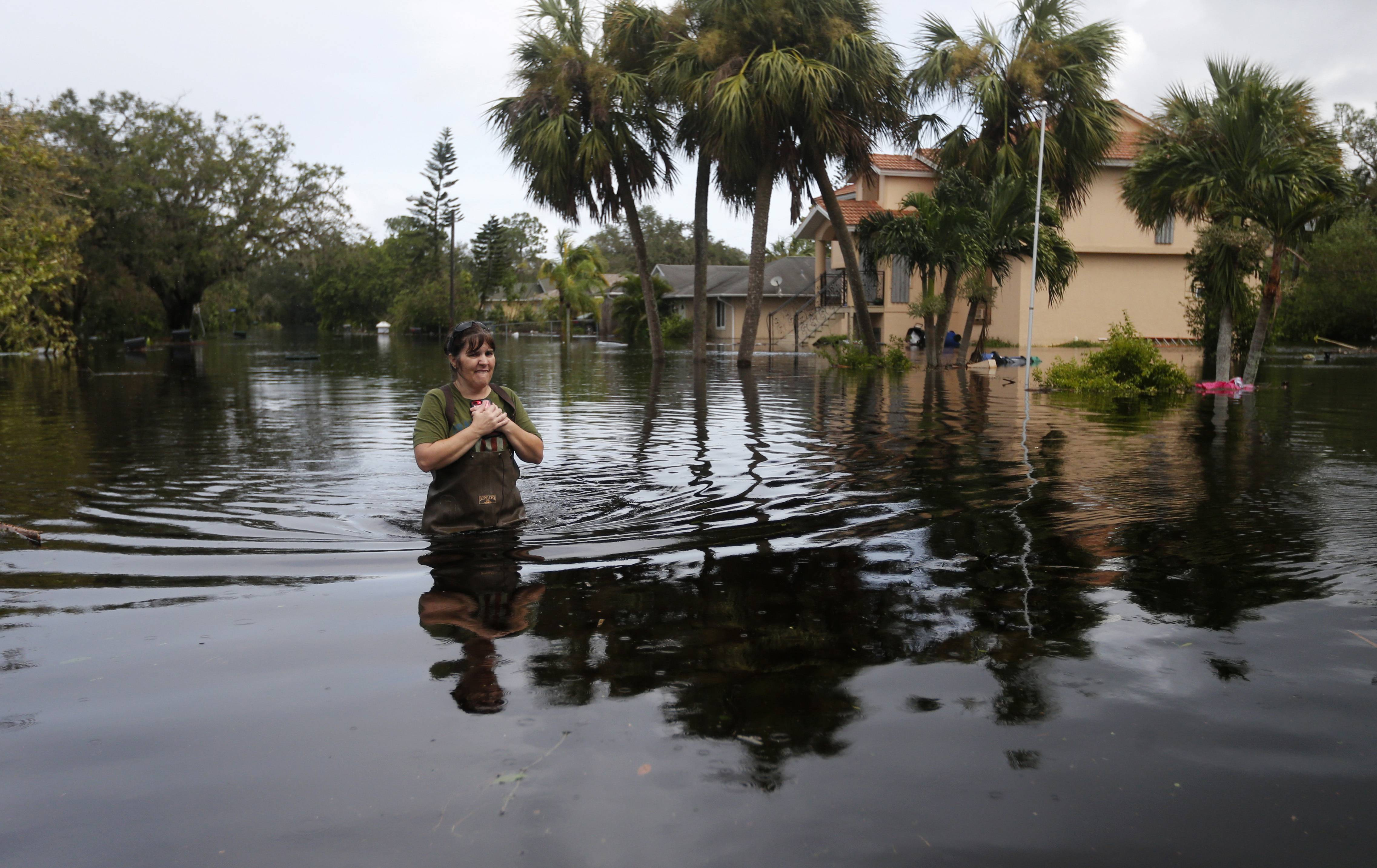 Kelly McClenthen walks through her flooded neighborhood Monday as she returns to see the damage to her home in the aftermath of Hurricane Irma in Bonita Springs, Florida.