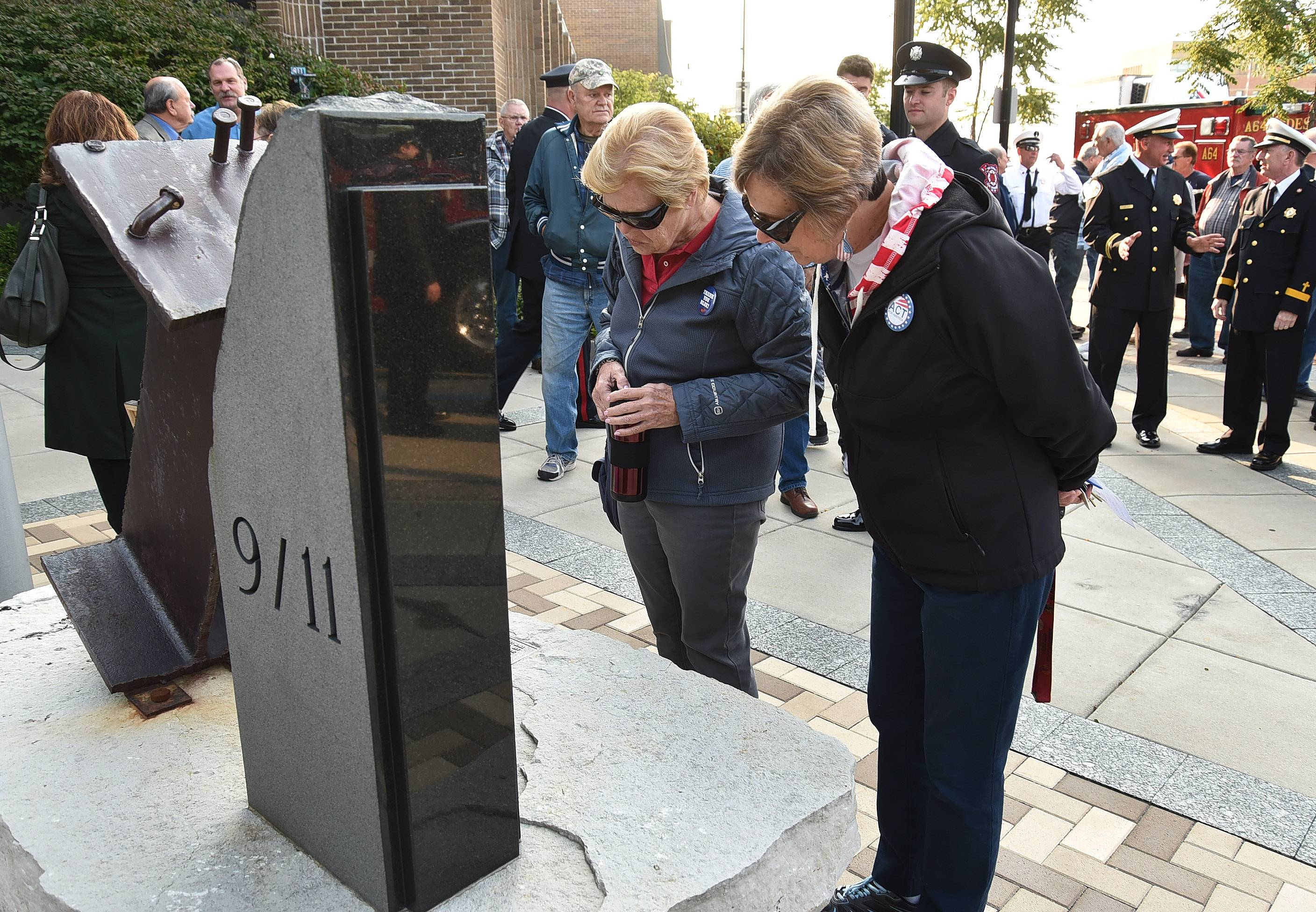 Sara Schmidt, left, and Fran Volpe take a closer look at the Des Plaines 9/11 memorial during the Sept. 11 remembrance ceremony at city hall.