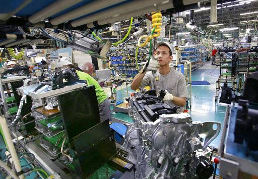 "In this Aug. 2, 2017, photo, Nissan Motor Co. factory workers check engines on an assembly line at its plant in Yokohama, near Tokyo. Aiming to get an edge on its rivals in an intensely competitive industry, Japanese automaker Nissan says it's attempting to foster a corporate culture that will produce manufacturing innovations in leaps and bounds instead of steady incremental improvement. Its discussion of that effort is partly a swipe at bigger competitor Toyota Motor Corp. which for decades has favored the concept of ""kaizen� or fine tuning and bit-by-bit progress in auto manufacturing. (AP Photo/Shizuo Kambayashi)"