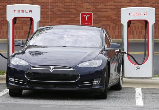 FILE - In this Saturday, June 24, 2017, file photo, a Tesla car recharges at a charging station at Cochran Commons shopping center in Charlotte, N.C. On Monday, Sept. 11, 2017, Tesla Inc. announced that more charging stations are on the way. The stations will be installed at places such as supermarkets and shopping centers, and in cities like Chicago and Boston. (AP Photo/Chuck Burton, File)