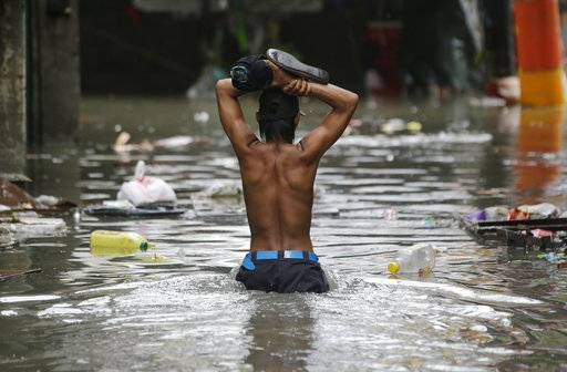 A resident wades through a flooded street as he returns to his home in Manila, Philippines, Tuesday, Sept. 12, 2017. Classes in schools and work in government offices have been suspended in the capital and nearby provinces as heavy rains pour causing floods in low-lying areas due to Tropical Depression Maring. (AP Photo/Aaron Favila)
