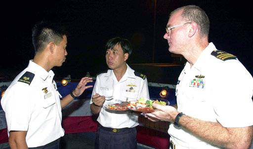 "FILE - This July 4, 2001, file photo provided by the U.S. Department of Defense shows U.S. Navy Commander Dave Kapaun, right, with Republic of Singapore Navy Major Danny Tan, left, and Republic of Singapore Major H .C. Lim at a reception on board the U.S. Navy dock landing ship USS Rushmore during the seventh annual Cooperation Afloat Readiness and Training (CARAT) Exercise. Retired U.S. Navy Commander Kapaun,who pleaded guilty to lying about his relationship with a Malaysian defense contractor nicknamed ""Fat Leonard"" is facing sentencing. (Kevin H. Tierney/U.S. Department of Defense via AP, file)"
