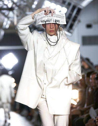 A model shields her eyes with a custom newspaper as she walks the runway at  the d28035b07960c