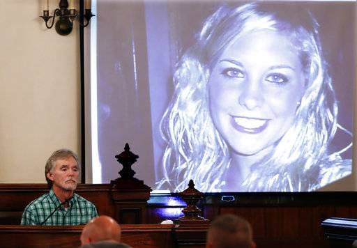 Dana Bobo, let, father of Holly Bobo, testifies in the trial of Zachary Adams as a photo of Holly Bobo is displayed Monday, Sept. 11, 2017, in Savannah, Tenn. Holly Bobo, a 20-year-old nursing student, disappeared from her home in Parsons, Tenn. on April 13, 2011, and Adams is charged with her kidnapping, rape and murder. (AP Photo/Mark Humphrey, Pool)