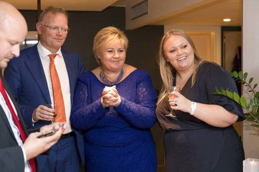 Norway's Prime Minister, Erna Solberg, centre, her husband Sindre Finnes, left, and her daughter Ingrid Solberg Finnes react to the results of Solberg's Conservative party, Høyre, with Solberg's advisor Sgbjorn Aanes, left, in Oslo, Monday, Sept. 11, 2017. The conservative parties that have governed Norway for the past four years appear to be retaining control of the parliament. (Hans Kristian Thorbjornsen/NTB scanpix via AP)