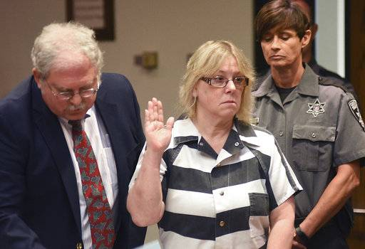 FILE - In this July 28, 2015 file photo, Joyce Mitchell raises her hand during a court appearance in Plattsburgh, N.Y. The state parole board on Friday, Sept. 8, 2017, denied parole to Mitchell, who played a key role in a prison break from the maximum-security state prison in Dannemora in June 2015. (Rob Fountain/The Press-Republican via AP, Pool, File)