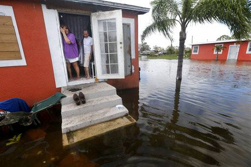 Quintana and Liz Perez look out at the flooding outside their home in the aftermath of Hurricane Irma in Immokalee, Fla., Monday, Sept. 11, 2017. (AP Photo/Gerald Herbert)