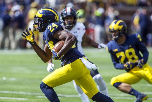 Michigan defensive back Lavert Hill (24) returns an interception for a touchdown in the fourth quarter of an NCAA college football game against Cincinnati in Ann Arbor, Mich., Saturday, Sept. 9, 2017. Michigan won 36-14. (AP Photo/Tony Ding)