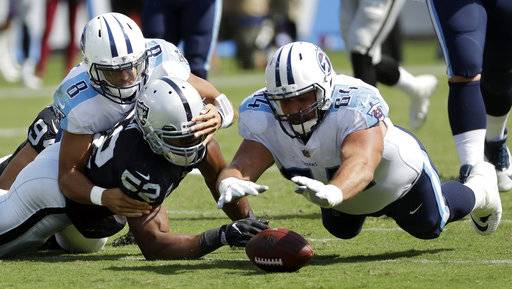 Tennessee Titans offensive guard Josh Kline (64) recovers a fumble by quarterback Marcus Mariota (8) as Oakland Raiders defensive end Khalil Mack (52) also scrambles for the ball in the second half of an NFL football game Sunday, Sept. 10, 2017, in Nashville, Tenn. (AP Photo/James Kenney)