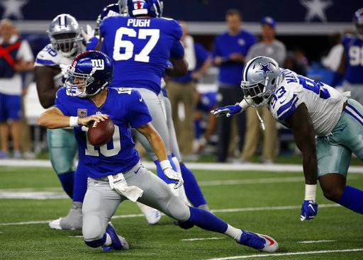 New York Giants quarterback Eli Manning (10) attempts to get rid of the ball under pressure from Dallas Cowboys defensive end Benson Mayowa (93) in the second half of an NFL football game, Sunday, Sept. 10, 2017, in Arlington, Texas. (AP Photo/Ron Jenkins)