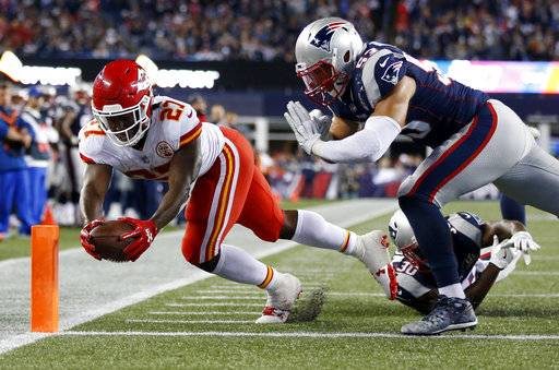 Kansas City Chiefs running back Kareem Hunt (27) crosses the goal line to score a touchdown past New England Patriots safety Duron Harmon, center, and linebacker Kyle Van Noy, top right, during the second half of an NFL football game, Thursday, Sept. 7, 2017, in Foxborough, Mass. (AP Photo/Michael Dwyer)