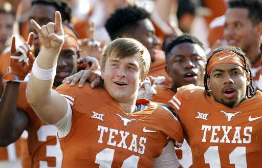 Texas quarterback Sam Ehlinger, left, defensive back P.J. Locke III, right, sing the school song following their win over San Jose State in an NCAA college football game, Saturday, Sept. 9, 2017, in Austin, Texas. Texas won 56-0. (AP Photo/Eric Gay)