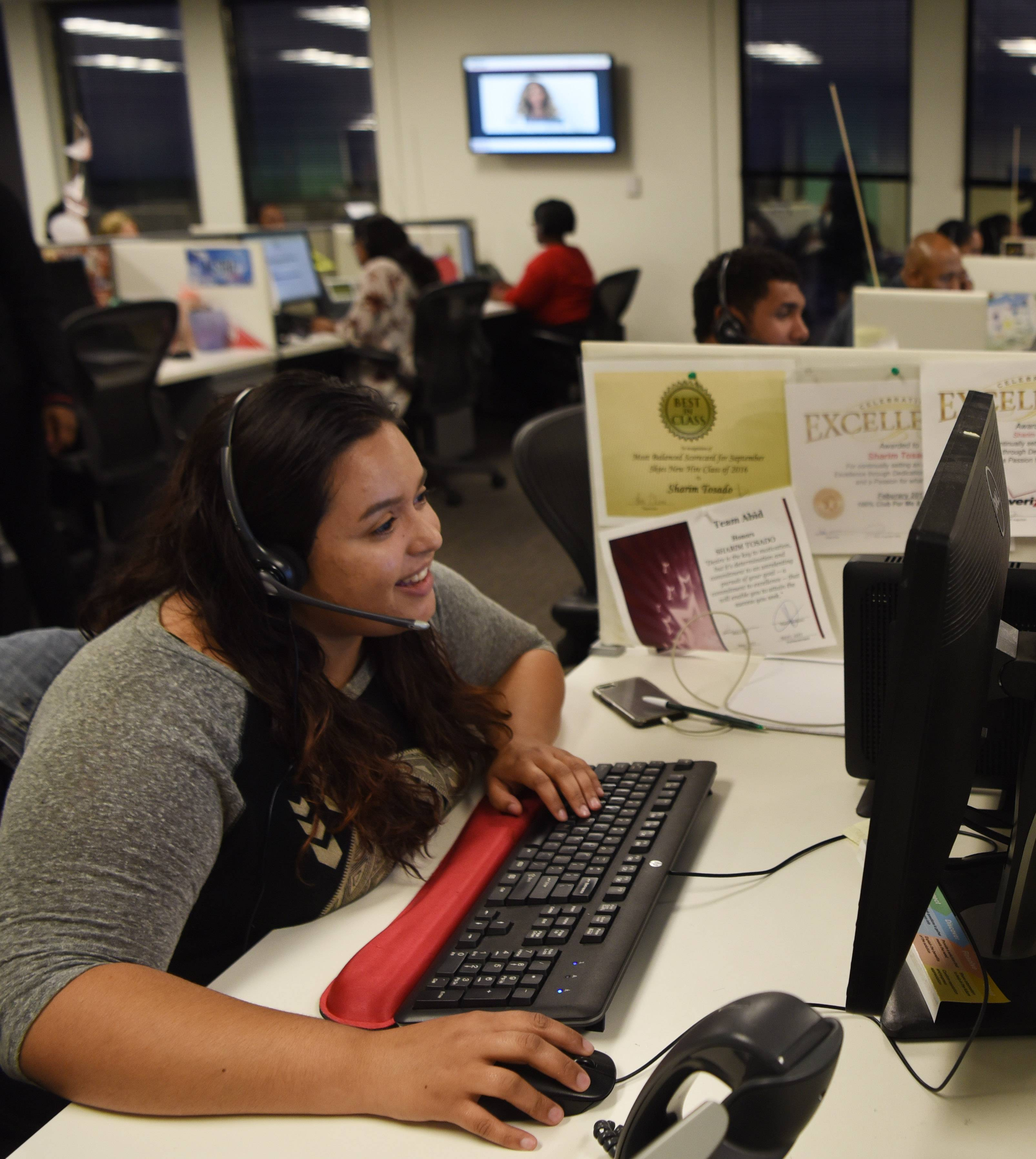 "Verizon Wireless volunteer Dainah Malave takes calls Tuesday night in Rolling Meadows during the ""Hand in Hand: A Benefit for Hurricane Relief"" telethon being broadcast live nationally."
