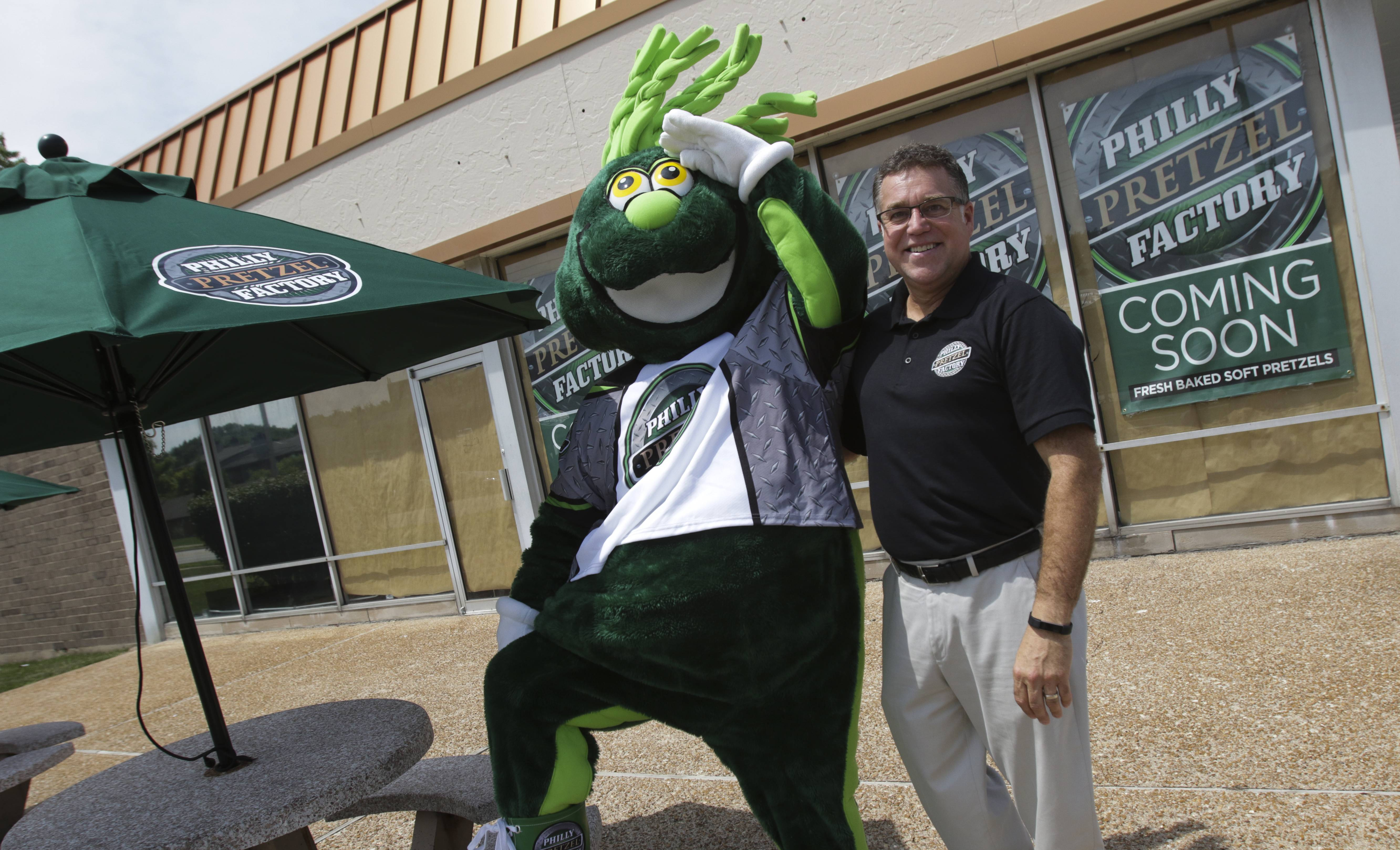 T.J. Berk plays the pretzel mascot Phil E. at Philly Pretzel Factory in Naperville, which franchise owner Tom Berk plans to open this month.